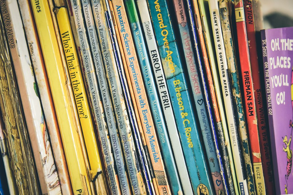 A row of very used books lined up  with the spines facing you. Most visible is the book on the extreme right, which is 'Oh, The Places You'll Go!'. Others include 'Fireman Sam', 'Errol the Peril' and 'Who's That in the Mirror?'